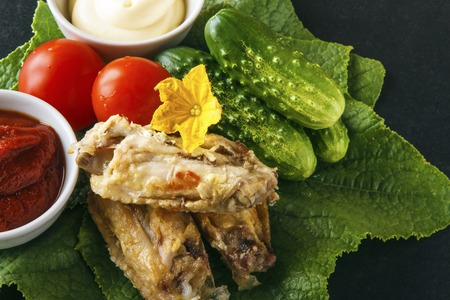 Fried chicken wings with fresh cucumber and tomatoes on a green cucumber leaves on a black background. Copy space.