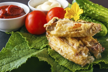Baked delicious chicken wings in tomato paste and mayonnaise on a green cucumber leaves with fresh organic vegetables on a black background. Healthy rustic food. Banco de Imagens