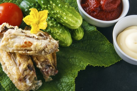 Healthy delicious chicken wings on a green cucumber leaves with fresh organic vegetables on a black background. Dietary rustic food. Copy space. Banco de Imagens - 106848710