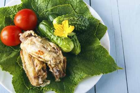 Healthy delicious chicken wings on a green cucumber leaves with fresh organic vegetables on a wooden table. Dietary rustic food. Copy space.