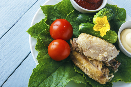 Fresh cooked delicious poultry wings on a green cucumber leaves with organic tomatoes on a white plate. View from above on wooden table. Copy space. Banco de Imagens - 106848712