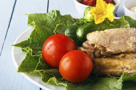 Organic tomatoes and gherkins on cucumber leaves on a white plate. Dietary food from chicken wings and natural vegetables. Copy space. Banco de Imagens - 106848713