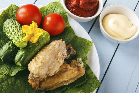 Dietary food from chicken wings and natural organic vegetables. Tomato paste and mayonnaise on wooden table. Copy space.
