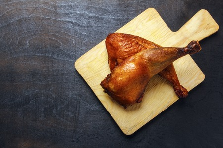 Chicken legs, cooked on a grill on a wooden cutting board. Top view. Copy space.