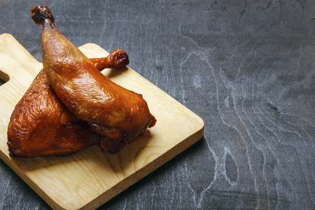 Chicken legs cooked on a grill on a cutting board on a black background. Copy space for text.