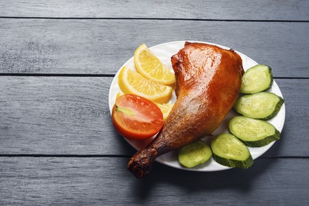 Crispy chicken legs, roasted on a grill with sliced lemon, cucumber and tomatoes on white plate on a wooden table. Copy space.