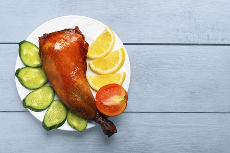 Crispy poultry meat, cooked on a grill with sliced lemon, cucumber and tomatoes on white plate on a wooden table background. Copy space. Top view from above. Banco de Imagens - 107604580