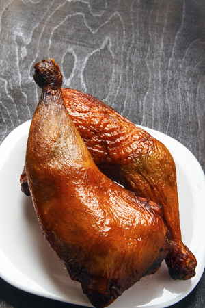 Dietary chicken legs cooked on a grill on a white plate on a black background in closeup. Top view from above. Copy space.
