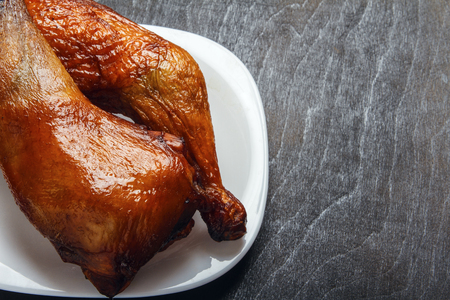 Chicken legs cooked on a grill on a white plate on a black background in closeup. Top view from above. Copy space. Natural food.