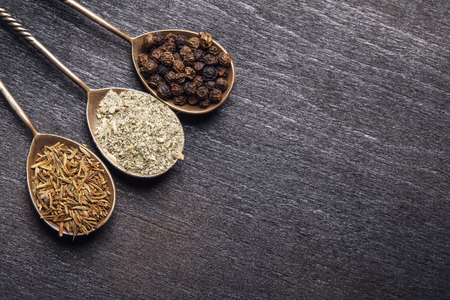 Silver spoons with natural spices on black wooden background. Top view from above. Copy space. Banco de Imagens