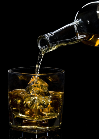 Whiskey being poured into a glass against black background Stock Photo