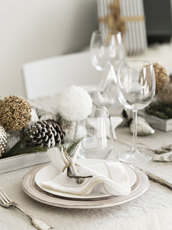 Table served for Christmas, New Year dinner in living room. Plate with linen napkin, napkin holders, pine cones, wine glass. Styled with an old-fashioned decoration in natural colors and stars.