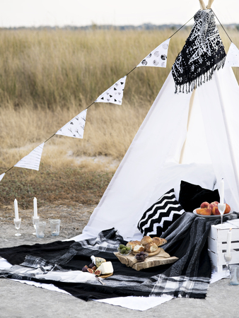 Stylish black and white picnic on the shore of  northern sea. Classic monochrome plaid, flag, tipi, candles and food.