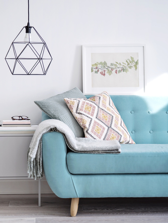 Levendige bank versierd met kussens en wollen plaid, kleine kast onder stijlvolle lamp in heldere zonovergoten kamer met minimaal design. Woonkamer concept.