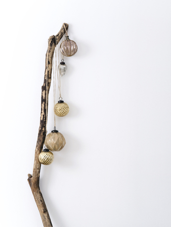 Minimalist composition of wood stick with hanging shiny baubles for Christmas concept. Фото со стока