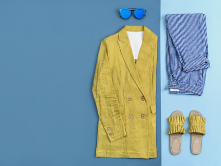 Summer fashion clothing and accessories flat lay. Urban female outfit on two-colored background: arranged on the right side yellow linen jacket, striped blue cotton pants, cobalt blue sunglasses and yellow textile sandals. Top view, space for text.