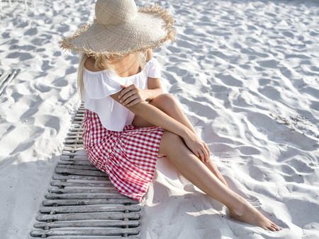 Happy relaxed blond young woman in white flounced top and a straw hat sits on a beach white sand enjoying the summer and morning sun. Summer vacations or holidays concept. Shallow depth of field, focu