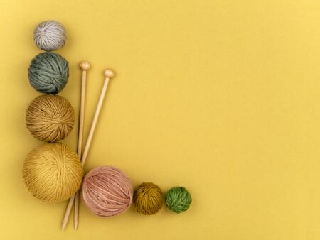 Wooden needles and various color balls of yarn on yellow background. Craft, knitting or hand made concept. Winter hobby frame. Top view, flat lay. Horizontal image. 스톡 콘텐츠