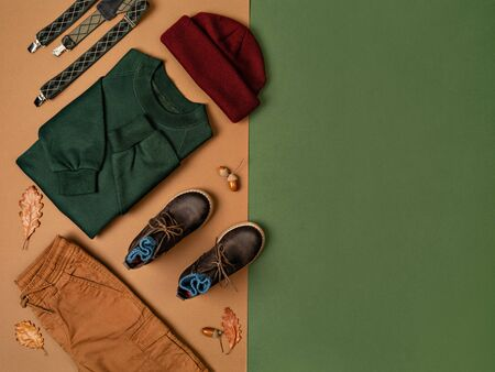 Autumn boy outfit on double colored green and brown backdrop. Little Boy Fashion, Autumn Fashion. Colorful kids sweatshirt, pants, hat and boots arranged with acorns and oak leaves. Autumn background. Thanksgiving day concept. Flat lay, top view.