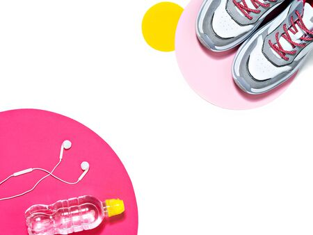 Top view of an pair of sport shoes, bottle of water and earphones on the pink and yellow circles background. Reducing weight, getting fit and healthy life style concept. Sport and fitness themed frame.