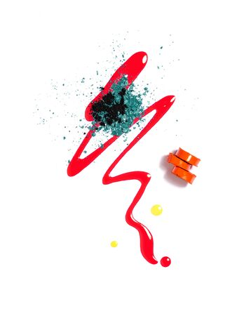 Spilled liquid lip gloss, sliced orange lipstick and crashed eyeshadows isolated on a white background. Lip, eye and nail makeup products. Creative composition of face makeup or decorative cosmetics samples. Beauty and makeup concept. Banco de Imagens