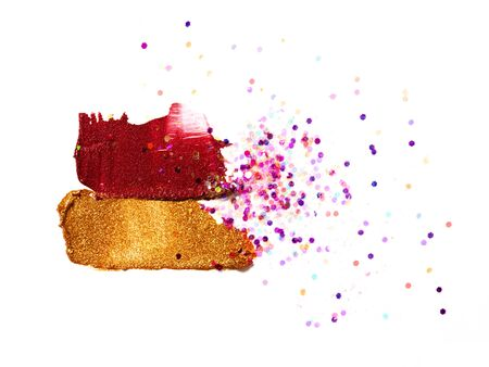 Shimmering golden and wine red lipstick strokes isolated on white background. Glittering eyeshadow smears with scattered confetti. Creative image of decorative cosmetics samples. Smudged cosmetic products. Beauty and makeup concept.