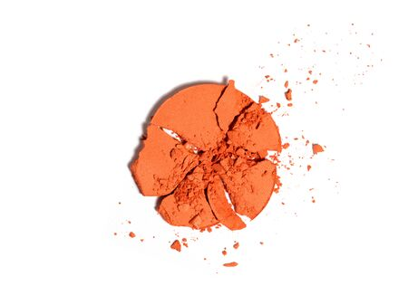 Top view of crushed round orange eyeshadow sample isolated on white. Crushed or broken cosmetics product. Makeup and cosmetics background. Banco de Imagens