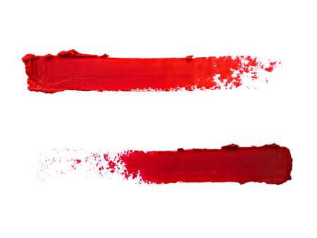 Wine-red and scarlet lipstick strokes made in opposite direction on white background. Creative image of decorative cosmetics samples. Smudged cosmetic products. Beauty and makeup concept.