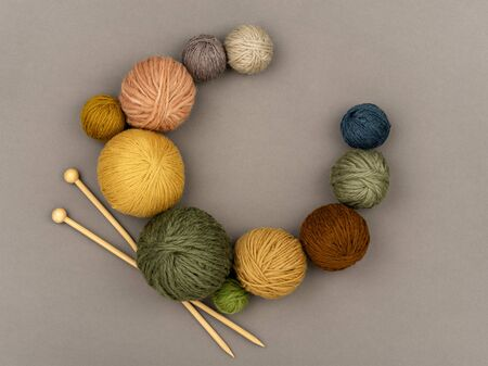 Various size and color balls of yarn arranged as a wreath with wooden knitting needles. Craft, knitting or hand made concept. Winter hobby background. Top view, flat lay, copy space for text.