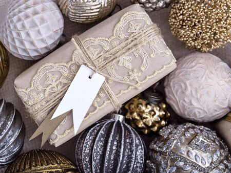 Close-up shot of a gift packed with craft paper, lace and twine arranged with old fashioned shiny baubles for Christmas tree. Winter holiday mood. New year, Christmas time background.