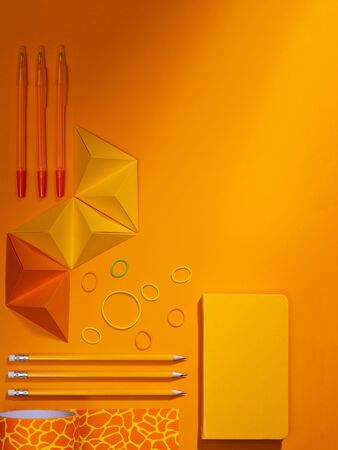 Monochromatic orange Stationery Supplies. Flat lay composition with orange pens, pencils, washi tape and notebook on orange background with origami decorative elements. Top view, copy space for text.