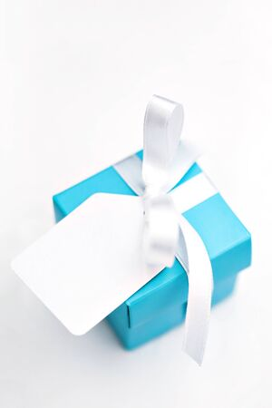 Top angled view of turquoise blue gift box decorated with white satin ribbon and blank tag over white background. Single surprise gift box. Presents, celebration, Sant Valentine's theme. Copy space.