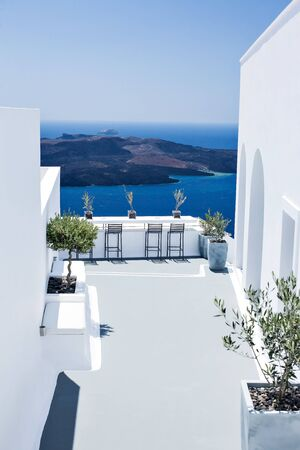 Splendida vista sul mare dalla terrazza bianca dell'hotel di lusso. Viaggio estivo e concetto di vacanza. Architettura bianca perfetta greca tradizionale e mare blu nella giornata di sole. Oia, isola di Santorini, Grecia.