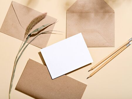 White empty paper card with stationery set of envelopes, notebook, pencil. Blank card styled mockup on beige background. To do list, greeting card or writing a letter concept.
