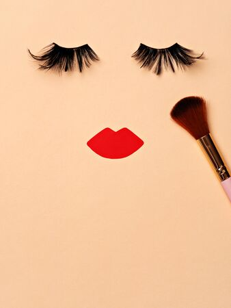 Abstract female face. Applying blush with makeup brush. False black lashes, red lips and shimmering blush on the beige background. Evening or stage makeup concept flat lay. Copy space for text. 版權商用圖片