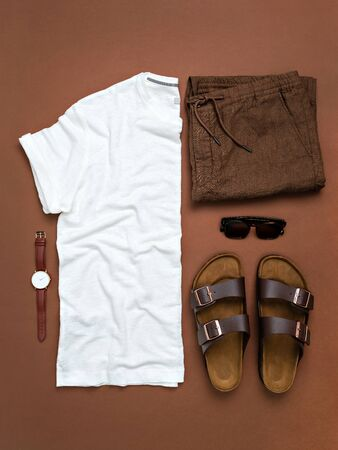 Top view of stylish male linen or cotton clothes on brown background. White blank t-shirt, folded pants and casual shoes with vintage sunglasses. Summer leisure or vacation idea.