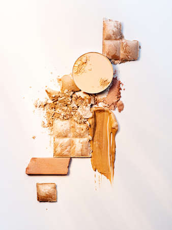Spills and smears of makeup foundation, eyeshadow, face powder and shimmering powder isolated on white