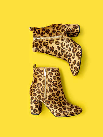Flat lay shooting of catchy female boots with high heels and leopard print placed on trendy illuminating yellow toned backdrop. Colour of the year 2021 background. Main colour trend concept.