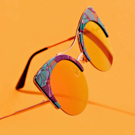 Marigold coloured retro shaped sunglasses of one color with background. Trendy colour of spring summer season. Eyes protection concept.