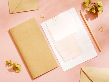 White empty handcrafted paper card with stationery set of envelopes, notebook, pencil on pink background. Blank vintage styled mockup with cute dried flowers and velvet ribbon. To do list, greeting card or writing a letter concept. Banque d'images