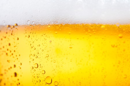 Fresh pils beer with froth and condensed water pearls photo