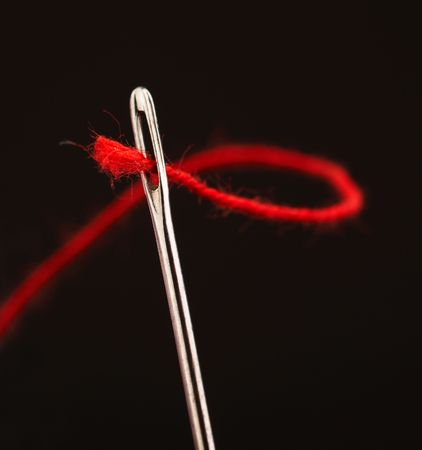 Red thread going through needle eye, closeup Stock Photo