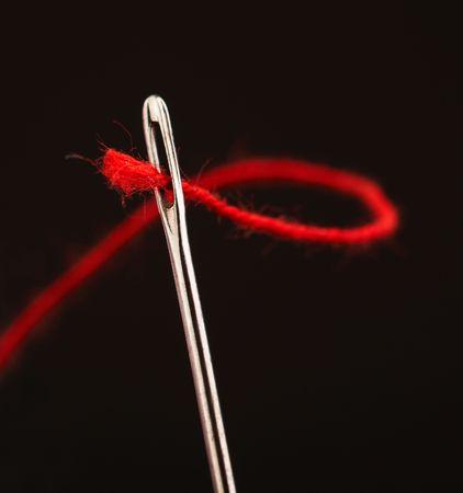 Red thread traverse une aiguille oeil, gros plan