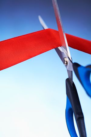Closeup image of scissors cutting a red ribbon Stock Photo