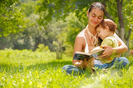 mom son: Happy mother and son reading a book outdoors
