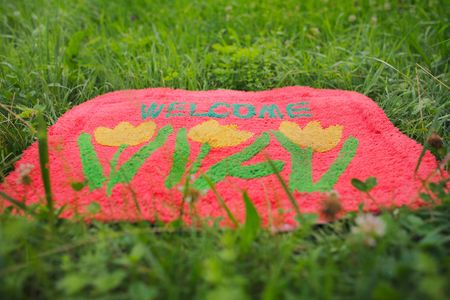 welcome mat: Photo of a welcome mat in front of a green meadow