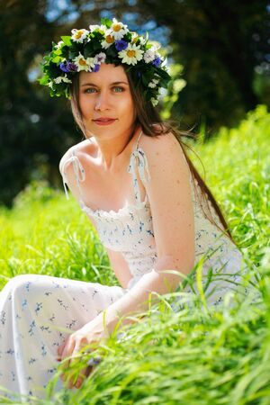 circlet: Portrait of a girl with circlet of flowers. She is sitting in a green meadow Stock Photo