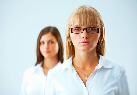 Two young  serious business women on light blue background whith a fair hair woman in focus Stock Photo - 5806960