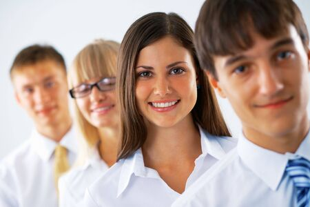 Happy business woman with her colleagues standing in a row.
