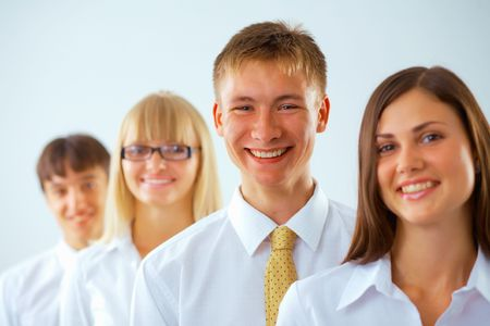 Portrait of young happy business man with his colleagues standing in a row photo